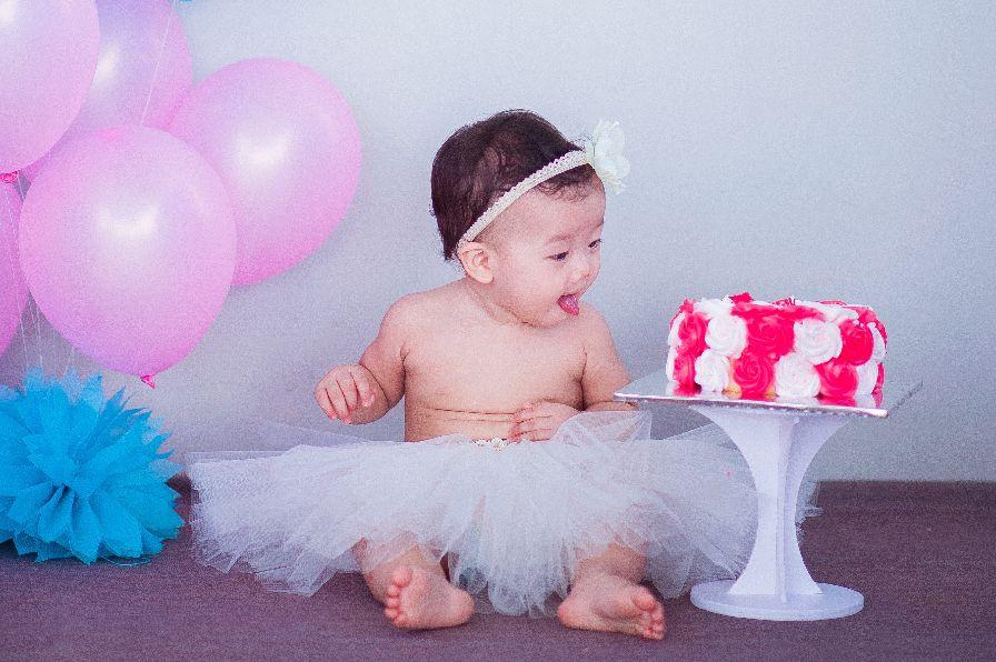 Baby schaut auf zuckersüße Torte