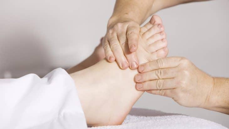 Ein Physiotherapeut behandelt den Fuss eines Patienten